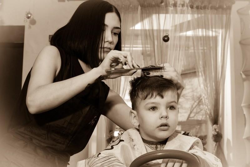 женщина стрижет ребенка