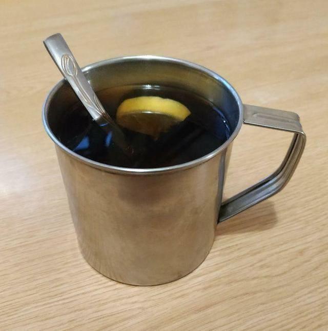кружка с чаем с лимоном и ложкой
