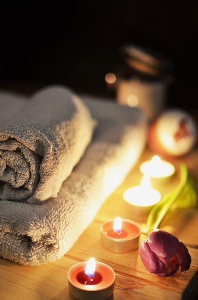 белые полотенца, свечи и цветок
