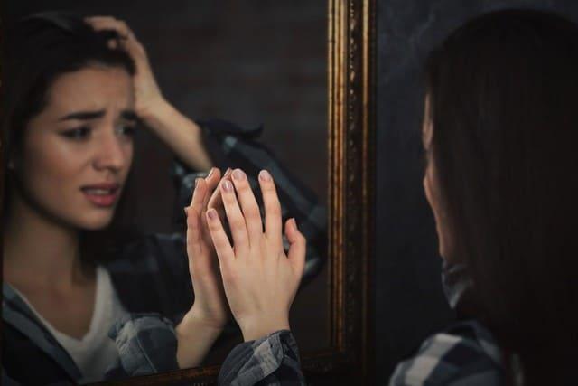 девушка плачет перед зеркалом