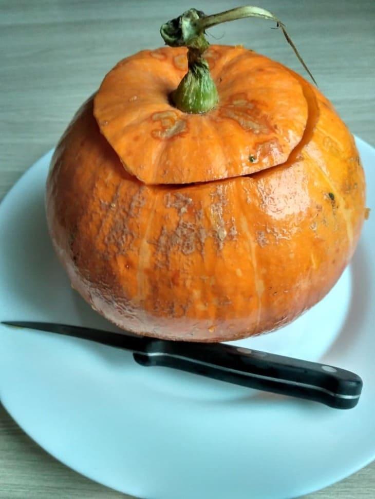 тыква с отрезанной верхушкой и нож на тарелке