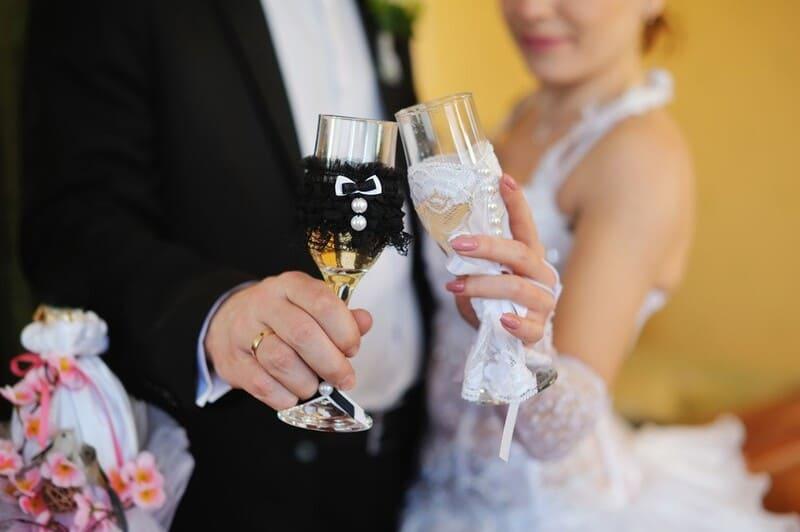 муж и жена чокаются бокалами на свадьбе