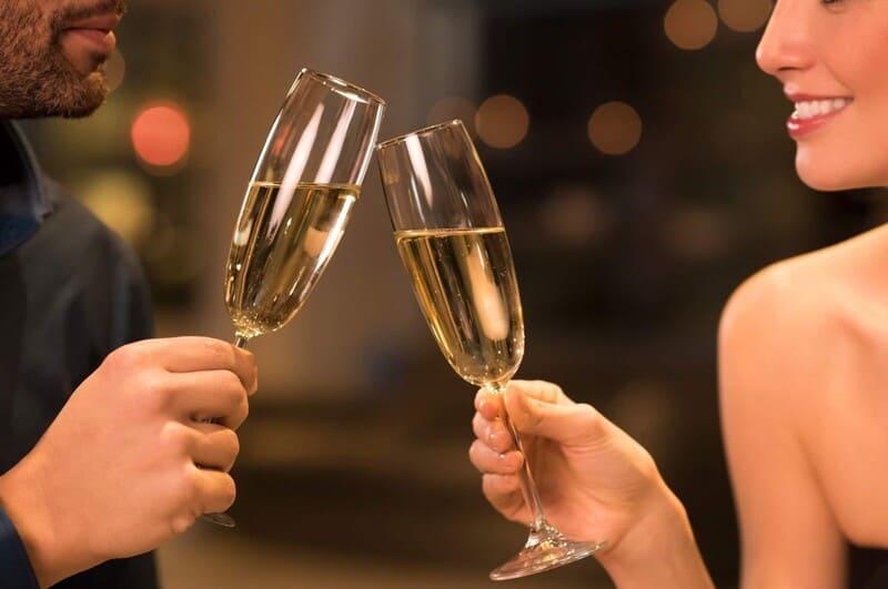 мужчина и женщина чокаются шампанским на свидании